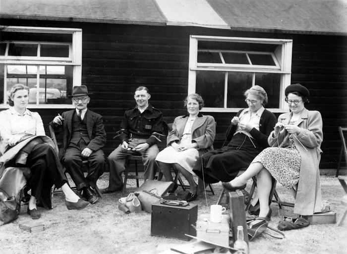 Photograph shows the social side of a shooting club, as the ladies relax outside the clubhouse - knitting, nattering and relaxing, while the chaps take a break too.