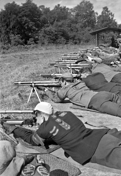 Photograph shows competitors taking aim from their firing points.