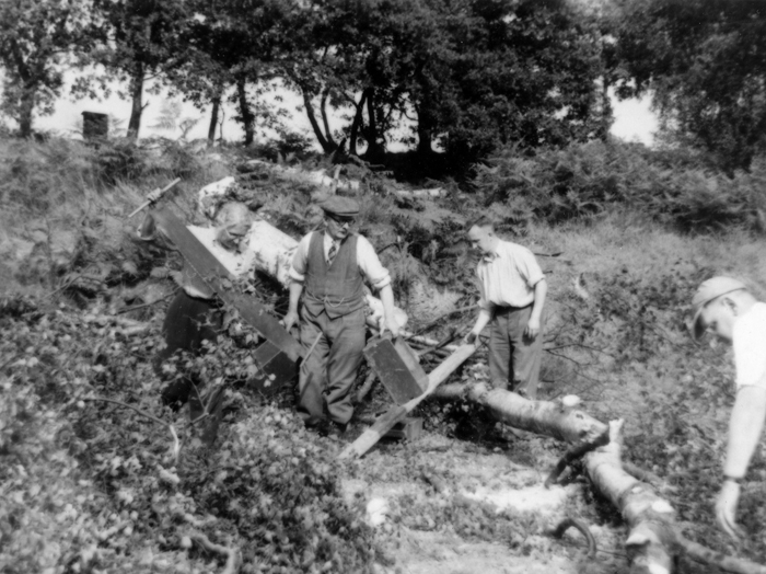 Photograph shows a group of very willing committee members and shooters clearing trees.