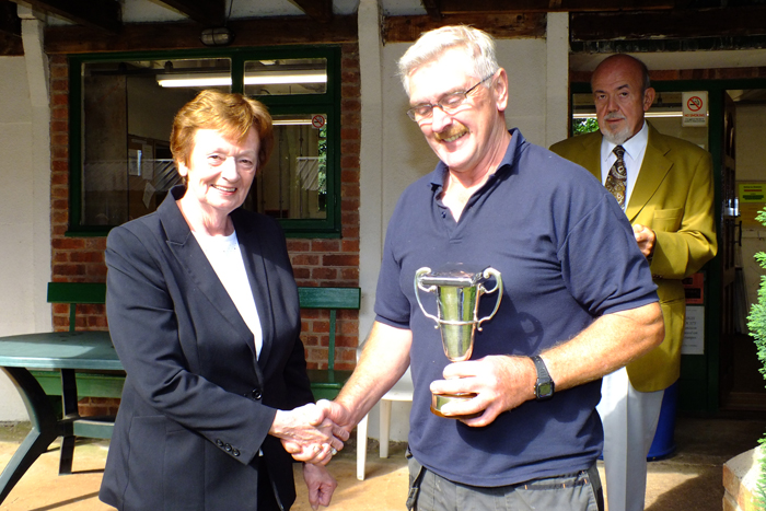 Photograph shows Mary Jennings, pictured left, presenting the Miniature Rifle Cup and 1st Place Medal to Peter Dean, pictured right.