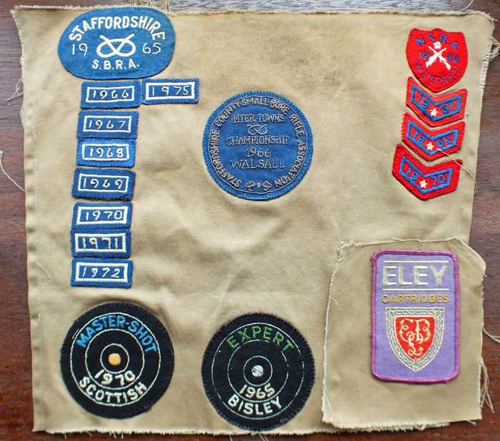 Photograph shows the back panel of a shooting jacket, bearing various shooting related badges.